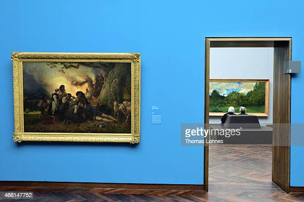 Visitors look at the painting 'French Orchard at Harvest Time' by CharlesFrancois Daubigny at Staedel Museum on March 13 2015 in Frankfurt am Main...