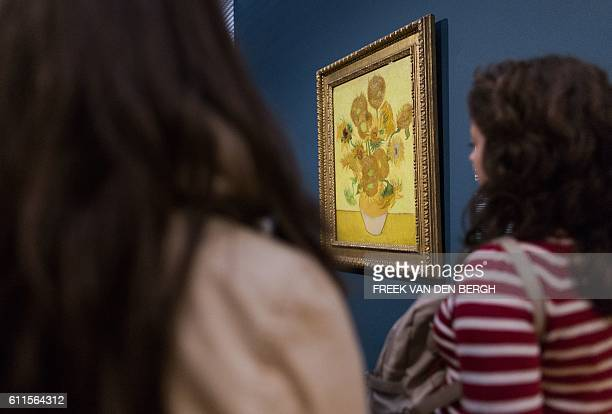 Visitors look at the painting 'Sunflowers' by Dutch painter Vincent van Gogh at the Van Gogh Museum in Amsterdam on September 30 2016 Two Van Gogh...