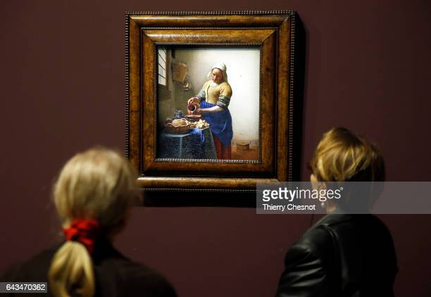 Visitors look at the painting 'The Milkmaid' by Dutch painter Johannes Vermeer during a press visit of the exhibition 'Vermeer and the Masters of...