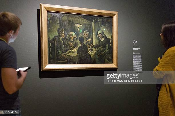 Visitors look at the painting 'The Potato Eaters' by Dutch painter Vincent van Gogh at the Van Gogh Museum in Amsterdam on September 30 2016 Two Van...