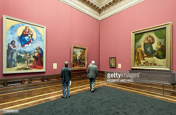 Visitors look at the paintings 'Sixtinische Madonna' and the 'Madonna di Foligno' wich are closely related by Italian artist Raphael and displayed at...