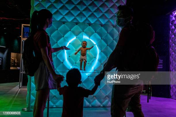 """Visitors look at the robot """"Animatronic baby"""" at the exhibition """"Robots, The 500-Year Quest to Make Machines Human"""" in the Hong..."""