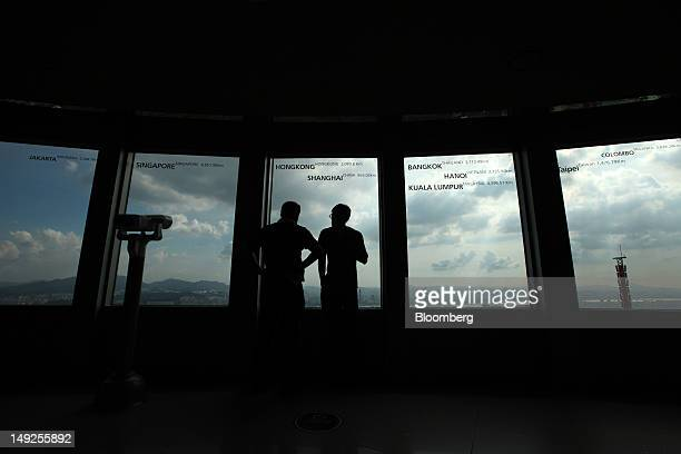 Visitors look at the skyline from an observation deck at the N Seoul Tower in Seoul South Korea on Tuesday July 24 2012 South Korea's economy grew at...