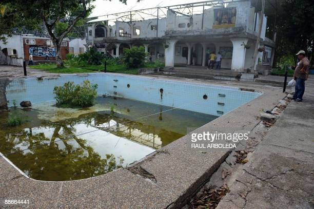 STORY Visitors look at the swimming pool and destroyed mansion of drug trafficker Pablo Escobar inside the Napoles ranch thematic park in Puerto...