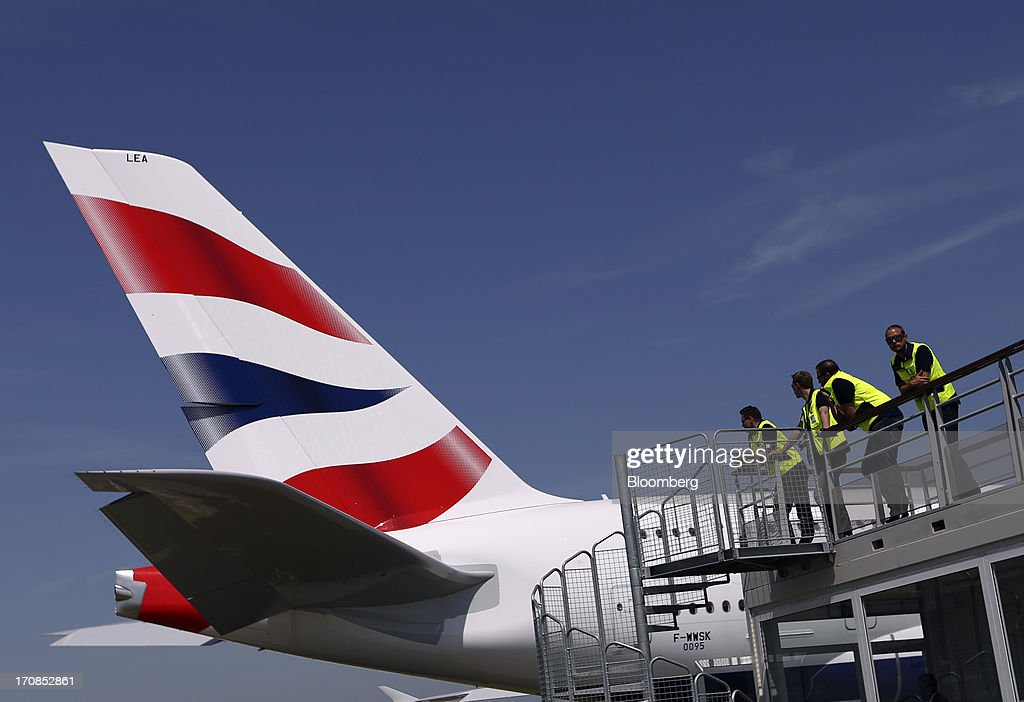 Visitors look at the tailfin of an Airbus SAS A380 aircraft, operated by British Airways, as it passes them on the tarmac on the first day of the Paris Air Show in Paris, France, on Monday, June 17, 2013. The 50th International Paris Air Show is the world's largest aviation and space industry show, and takes place at Le Bourget airport June 17-23. Photographer: Chris Ratcliffe/Bloomberg via Getty Images