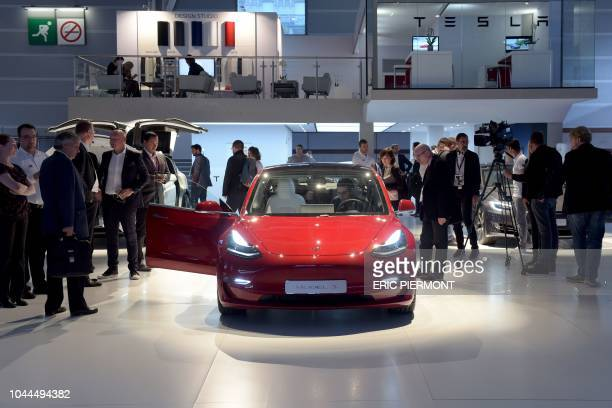 Visitors look at the Tesla model 3 on the Tesla stand during the press days of the Paris Motor Show on October 2 2018