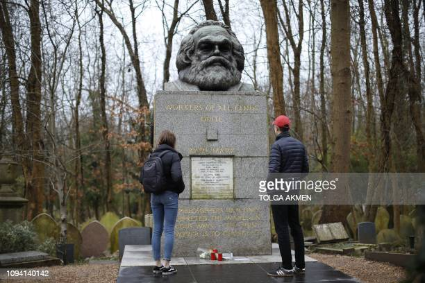 Visitors look at the tomb of German revolutionary philosopher Karl Marx a Grade Ilisted monument with the marble plaque on the front showing damage...