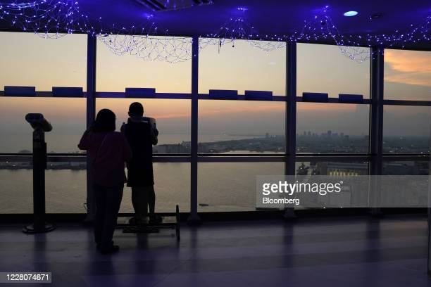 Visitors look at the view from the observation at Chiba Port Tower at dusk in Chiba, Japan, on Saturday, Aug. 15, 2020. Japans economy shrank last...
