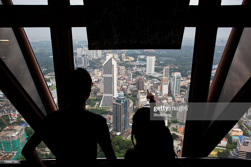 Visitors look at the view from the observation deck at Kuala Lumpur Tower in Kuala Lumpur, Malaysia, on Wednesday, Jan. 16, 2013. While many developed countries have faltered, Malaysia's gross domestic product growth has exceeded 5 percent for five quarters with domestic demand countering a slowdown in exports. Photographer: Lam Yik Fei/Bloomberg via Getty Images