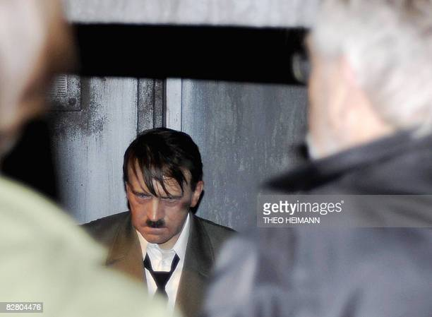 Visitors look at the waxwork statue of Adolf Hitler at Madame Tussauds waxworks museum in Berlin on September 13 2008 as it returend to the museum...