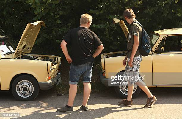 Visitors look at Trabant automobiles at a Trabant enthusiasts' weekend on August 8 2015 near Nossen Germany The Trabant also called the Trabi is the...