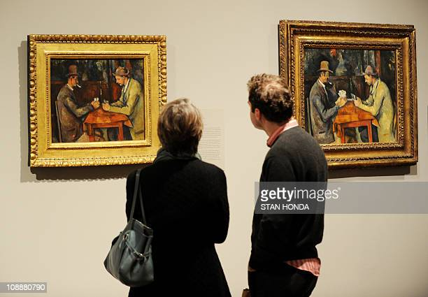 Visitors look at two versions of Paul Cézanne's 189092 The Card Players on February 7 2011 at the Metropolitan Museum of Art in New York during a...