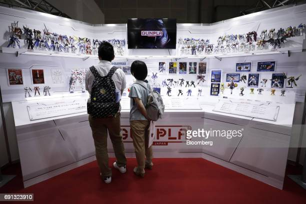 Visitors look at various plastic models from the Gundam Series on display at the Bandai Co booth at the International Tokyo Toy Show in Tokyo Japan...