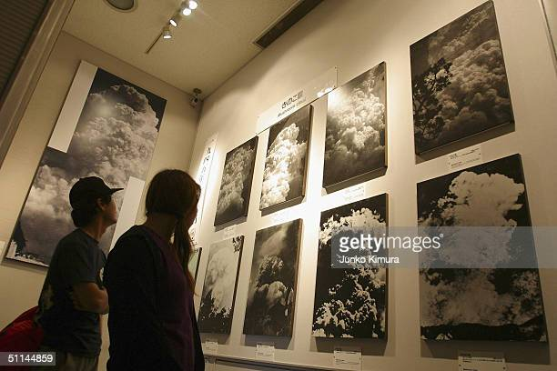 Visitors look at views of the mushroom cloud pictured when the atomic bomb was dropped August 5 2004 in Hiroshima Japan Tomorrow Hiroshima will mark...