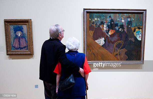 Visitors look at works of art entitled 'Jane Avril' and 'At The Moulin Rouge' by French artist Henri de ToulouseLautrec at the 'ToulouseLautrec and...