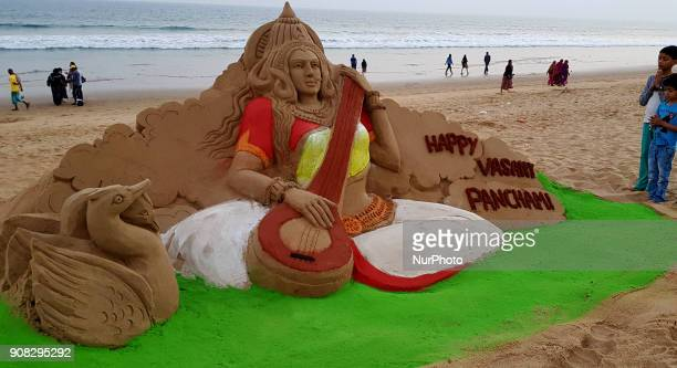 Visitors look near to the Goddess Saraswati's sand sculpture as it is creating by sand artist Manas Sahoo on the eve of Basanta Panchami or Saraswati...