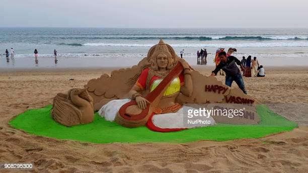 Visitors look near to the Goddess Saraswati's sand sculpture as it is creating by sand artist Manas Sahoo on the eve of Basanta Panchami or Saraswati...