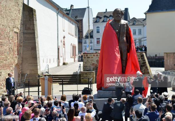 Visitors look on as a statue of German revolutionary thinker Karl Marx is being unveiled on May 5 2018 in his native city Trier southwestern Germany...
