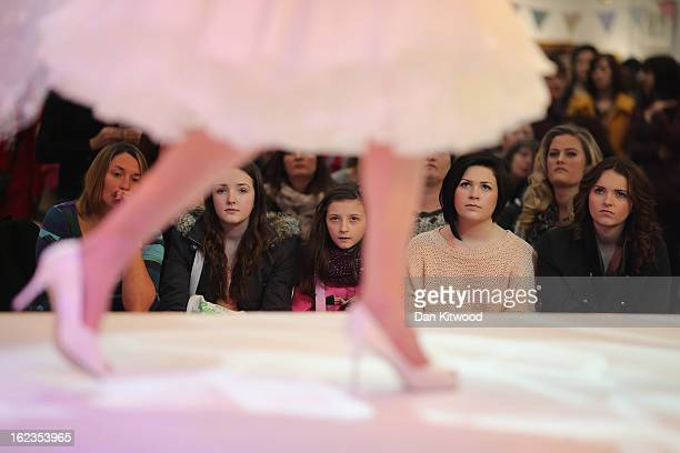 Visitors look on as models showcase wedding dresses on a catwalk show during the National Wedding Show at London's Olympia on February 22 2013 in...