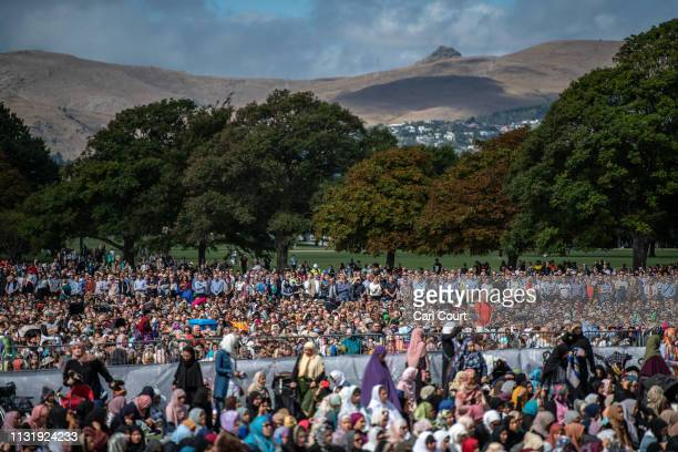 Visitors look on as Muslims attend Friday prayers in a park near Al Noor mosque on March 22, 2019 in Christchurch, New Zealand. 50 people were...