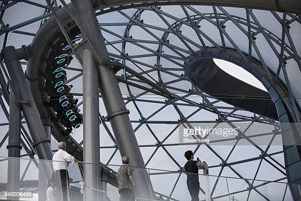 Visitors look on as the Tron Lightcyle Power Run rollercoaster operates at Walt Disney Co's Shanghai Disneyland theme park during a trial run ahead...