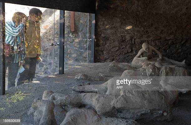 Visitors look on November 9, 2012 through the protective glass of the Orto dei fuggiaschi where are displayed 13 bodies of victims who were buried by...