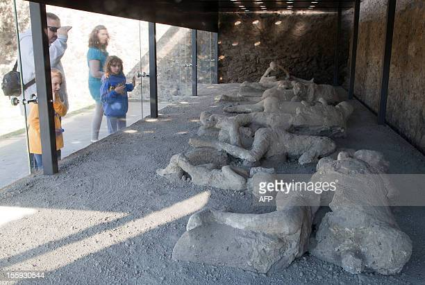 Visitors look on November 9 2012 through the protective glass of the Orto dei fuggiaschi where are displayed 13 bodies of victims who were buried by...