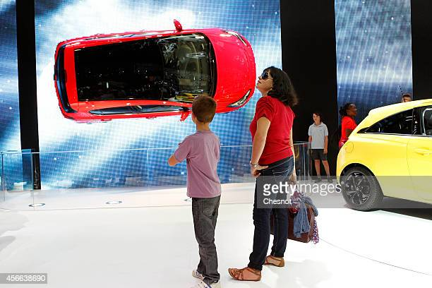 Visitors look Opel Corsa automobile at the Paris Motor Show on October 04 2014 in Paris France More than a million visitors are expected at the...