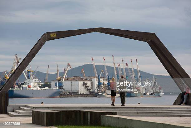 Visitors look out across the Golden Horn Bay waterway towards shipping cranes on the dockside in Vladivostok Russia on Sunday Sept 27 2015 'It is...