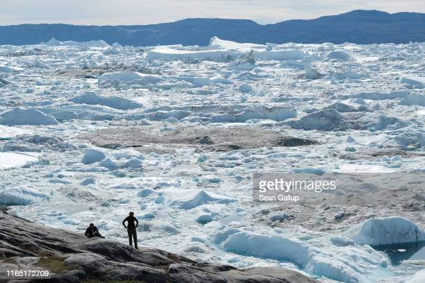 Visitors look out onto freefloating ice jammed into the Ilulissat Icefjord during unseasonably warm weather on July 30 2019 near Ilulissat Greenland...