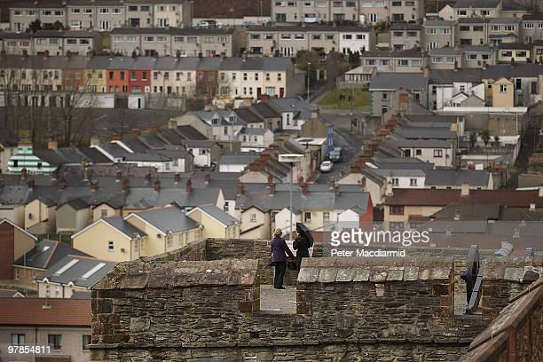 Visitors look out to the Catholic Bogside area from the City Walls on March 15 2010 in Derry Northern Ireland The Bloody Sunday Inquiry chaired by...