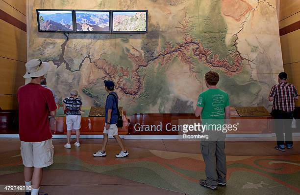 Visitors look over a large scale raisedrelief map in the visitors center at Grand Canyon National Park in Grand Canyon Arizona US on Wednesday June...