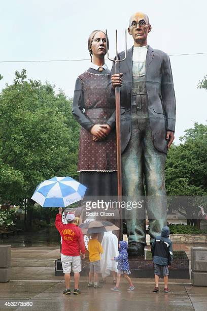 Visitors look over a statue of a farmer and his daughter depicted from Grant Wood's American Gothic painting on the fairgrounds of the Iowa State...