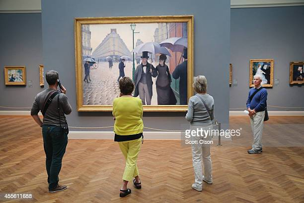 Visitors look over Paris Street; Rainy Day by the French artist Gustave Caillebotte at the Art Institute of Chicago on September 17, 2014 in Chicago,...