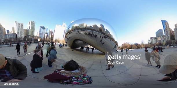 Visitors look over the Cloud Gate sculpture in Millennium Park on March 7 2017 in Chicago Illinois Cloud Gate also known as The Bean was created by...