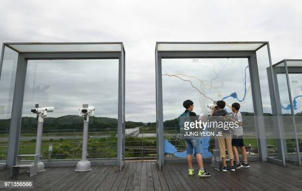 Visitors look through binoculars at a viewing deck of Imjingak peace park near the Demilitarised Zone dividing the two Korea's in the border city of...