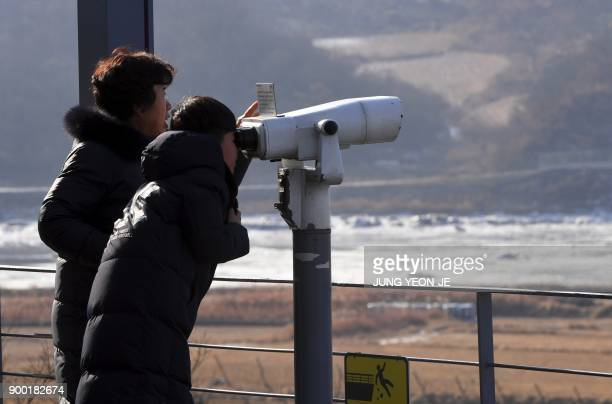 Visitors look through binoculars during a visit to the Imjingak peace park near the Demilitarized Zone dividing the two Koreas in the border city of...