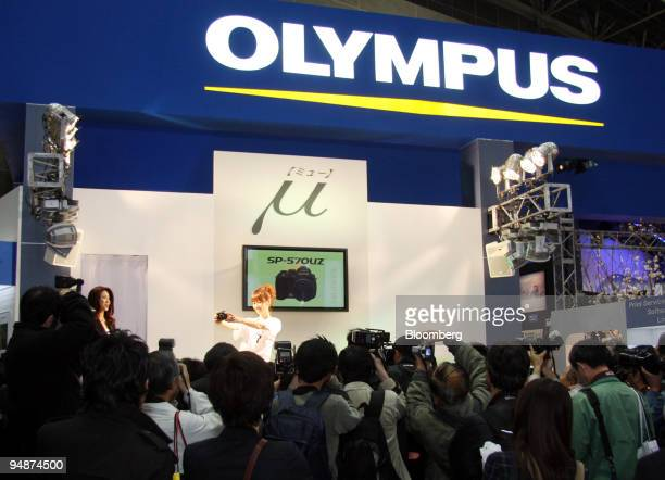 Visitors look through Olympus Corp's booth at the Photo Imaging Expo in Tokyo Japan on Wednesday March 19 2008 Olympus Corp is the world's largest...
