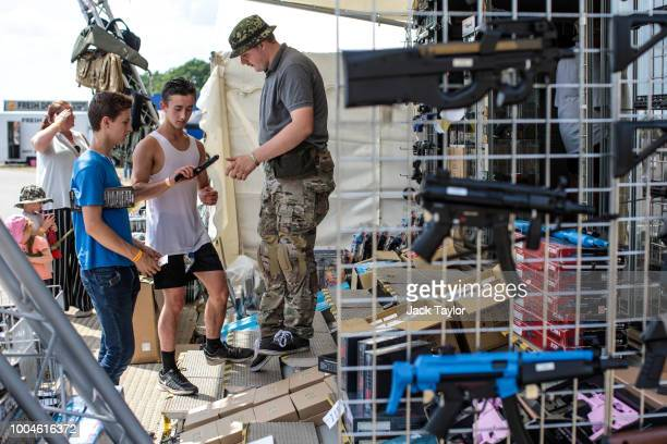 Visitors look through the airsoft guns on display during the annual War and Peace Revival show at Hop Farm Country Park on July 24 2018 in Maidstone...