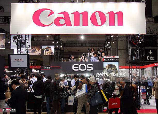 Visitors look through the Canon Inc booth at the Photo Imaging Expo in Tokyo Japan on Wednesday March 19 2008 Japan's electronics makers fell in New...