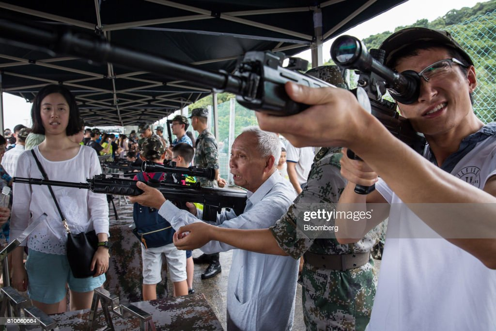 Visitors look through the scopes of rifles during an open day at the People's Liberation Army (PLA) Ngong Suen Chau Barracks in Hong Kong, China, on Saturday, July 8, 2017. China's bid to display some soft power in Hong Kong-- with a visit by the country's first aircraft carrier -- has also showcased its heavy-handed approach to security. Photographer: Billy H.C. Kwok/Bloomberg via Getty Images