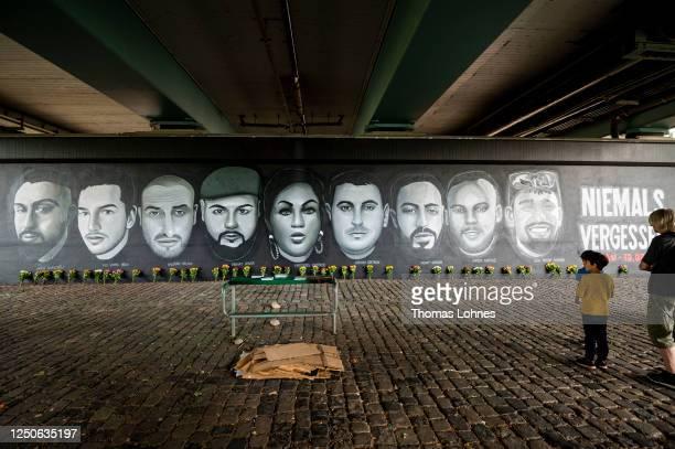 Visitors look to a 27 meter long street art mural to commemorate the nine victims of the 2020 Hanau shooting spree at Friedensbruecke bridge on June...