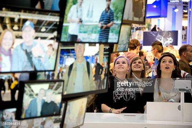 Visitors look up at an image of themselves on an electronic image tree at the Nikon stand at the Photokina trade fair in Cologne on September 19 2012...