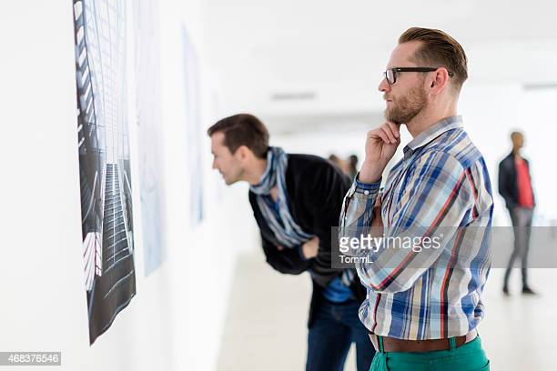 visitors looking at artwork - foto stockfoto's en -beelden