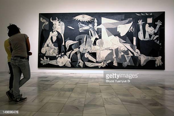 Visitors looking at Pablo Picasso's Guernica in Reina Sofia National Art Museum (Museo Nacional de Arte Reina Sofia).