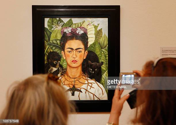 Visitors looks at a painting by Mexican artist Frida Kahlo titled 'SelfPortrait with Thorn Necklace and Hummingbird' during the opening of a show of...