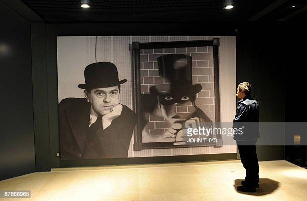 Visitors looks at a painting of the Belgian artist Rene Magritte at the press opening of the new Margitte museum in Brussels on May 20 2009 The...