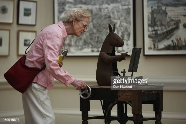Visitors looks at a piece of work during a press preview of the Royal Academy's 'Summer Exhibition' on June 5, 2013 in London, England. The 245th RA...