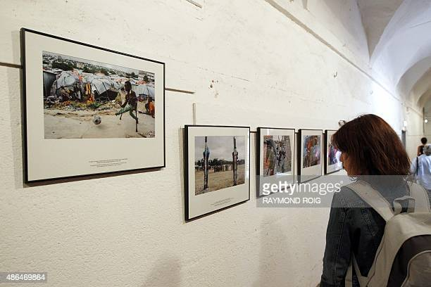 Visitors looks at Somali AFP photographer Mohamed Abdiwahab's photo series 'Crushed Somalia' displayed at the 27th photojournalism festival Visa pour...