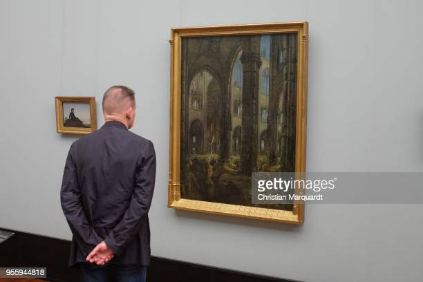 Visitors looks at the artwork 'Gotische Kirchenruine' by Carl Blechen during the exhibition preview for 'Wanderlust Von Caspar David Friedrich bis...